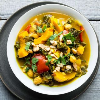An overhead view of a white bowl filled with vegetable curry topped with cilantro and cashews on a gray painted surface