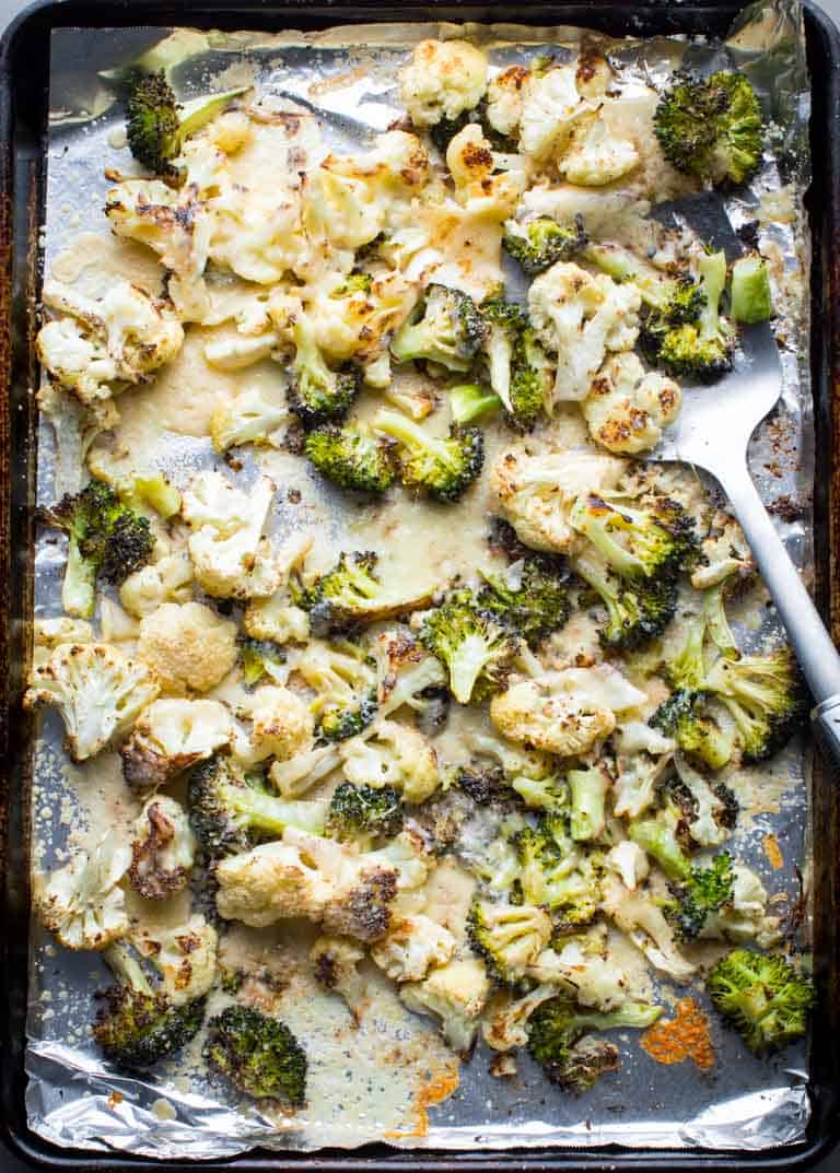 a foil-lined sheet pan with roasted cauliflower and broccoli with cheese melted over it.