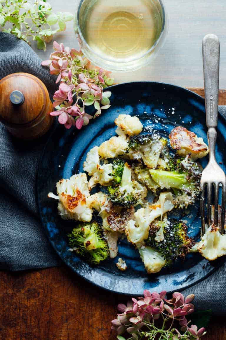 a blue plate with roasted broccoli and cauliflower with grated Parmesan sprinkled over it