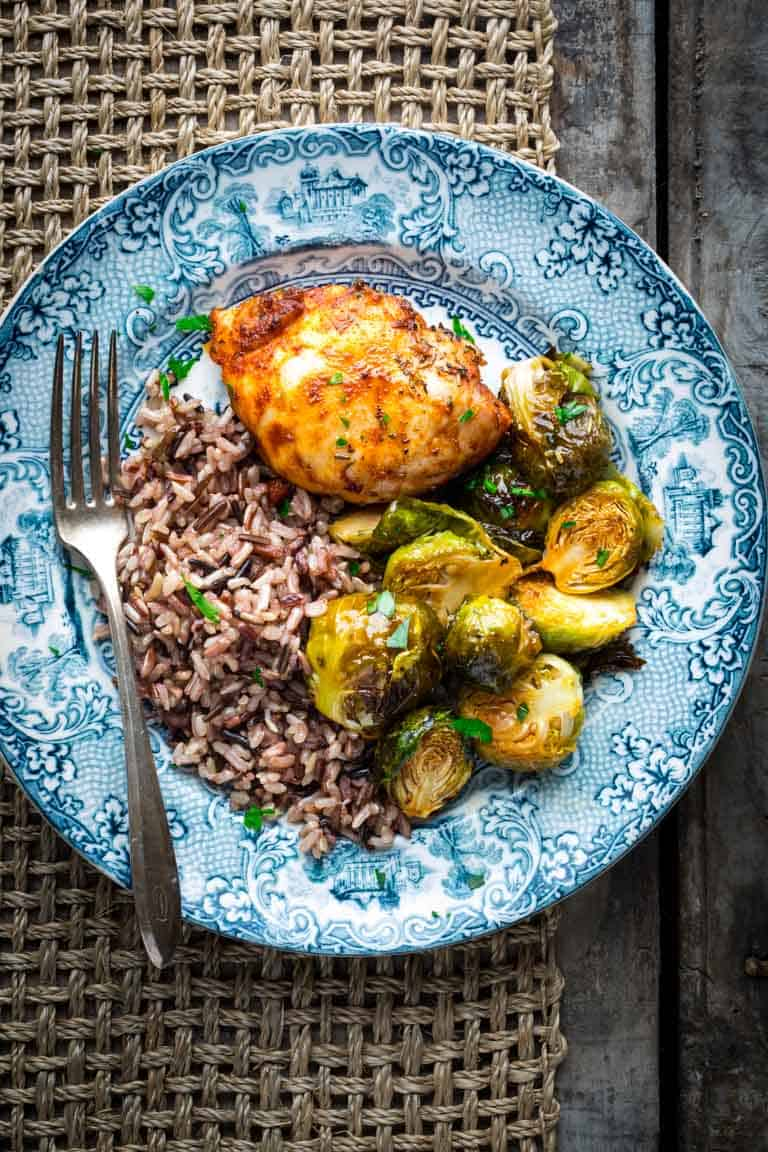 A blue plate with a chicken thigh, rice and roasted brussels sprouts.