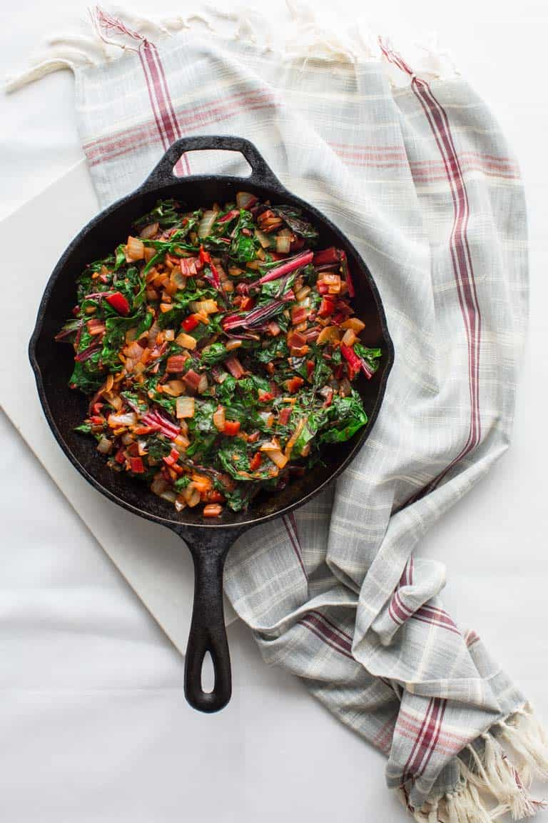 A white table and gray cloth with a skillet with chard in it