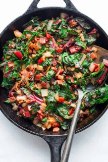 A black skillet with sautéed swiss chard, overhead