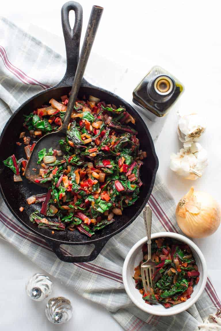 A black skillet with sautéed swiss chard, a bottle of vinegar and an onion overhead