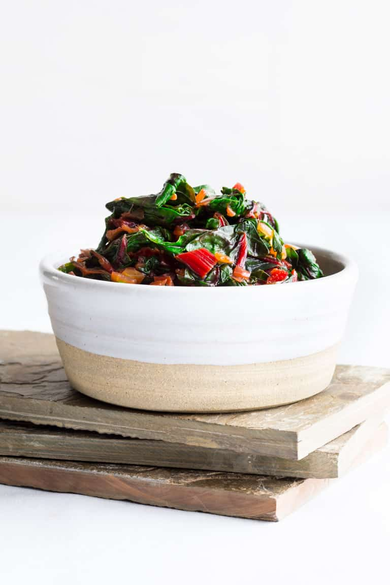 A white ceramic dish with sauteed swiss chard in it