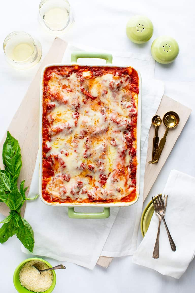 A white table with a white board with butternut squash lasagna