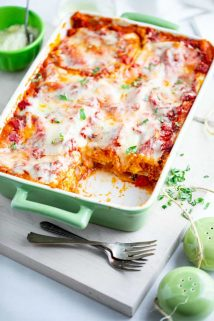 Butternut Squash Lasagna on a white board with two forks and some chopped basil