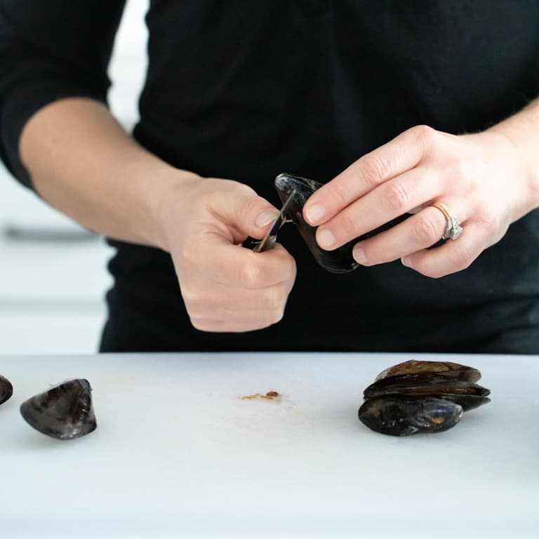 trimming the beard off a mussel