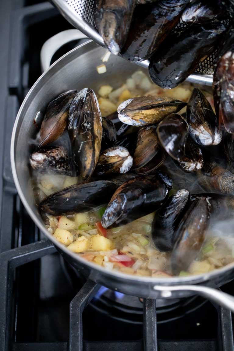 Add the mussels to the simmering liquid.