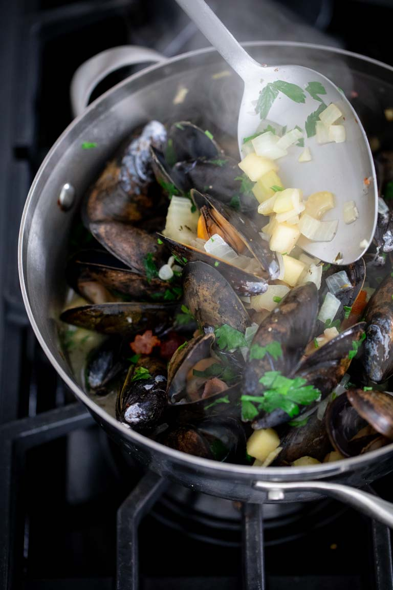 How to Cook Mussels: stir together to coat the cooked mussels in the flavorings and sauce.