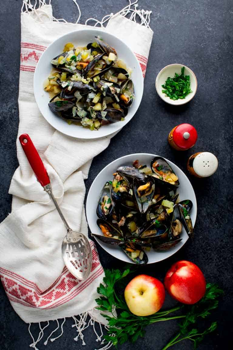 A black table with mussels in two bowls.