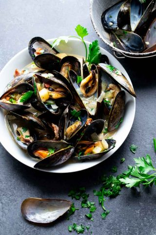A black table with a white bowl with mussels