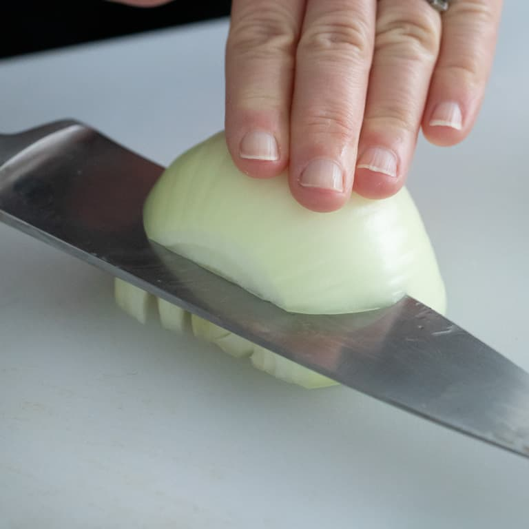 Slice onion into slabs stopping just before you get to the root end. The root end will hold the onion together as you slice it.