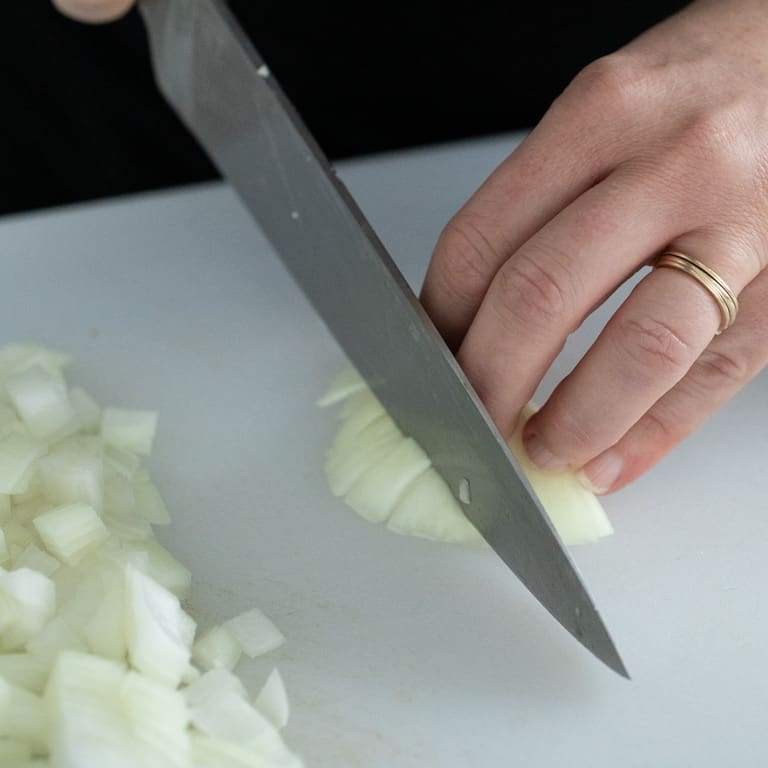Cut around the root end to use all edible parts of the the onion and limit waste.