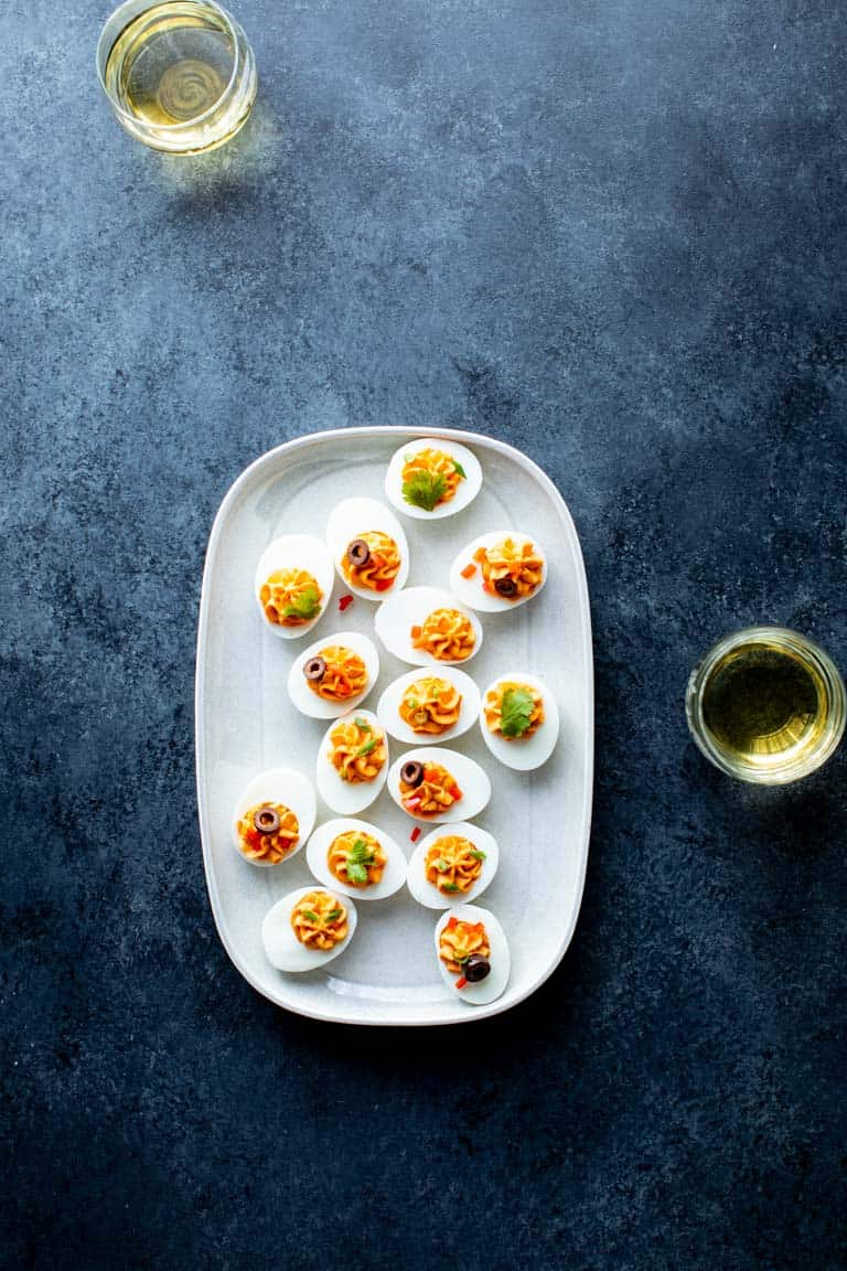 A black and gray surface with a platter of spicy deviled eggs on it and two glasses of wine