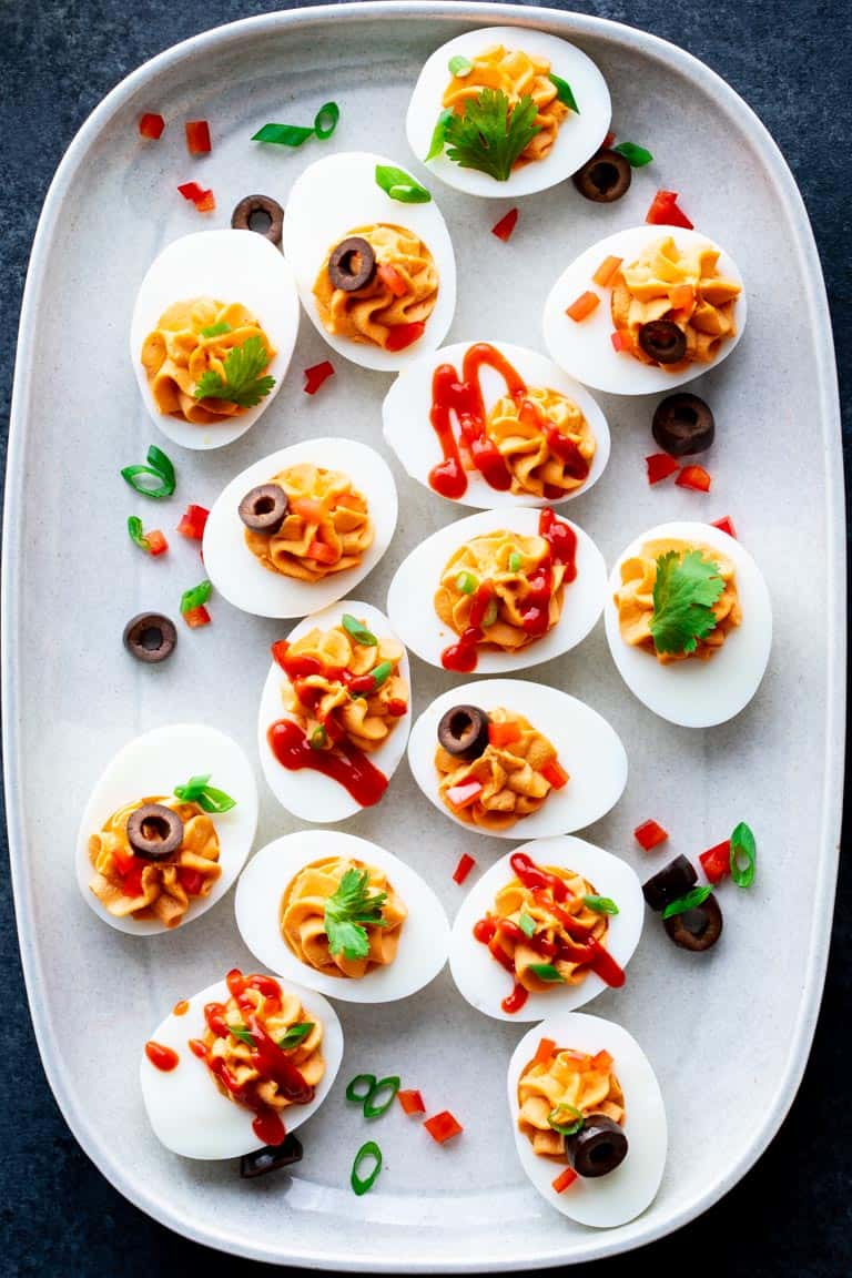 A white platter with spicy deviled eggs on it