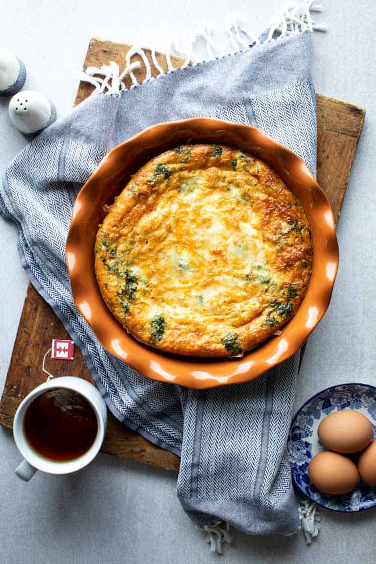 Spinach Egg Bake in a pie plate on a white table with a cutting board and blue kitchen towel