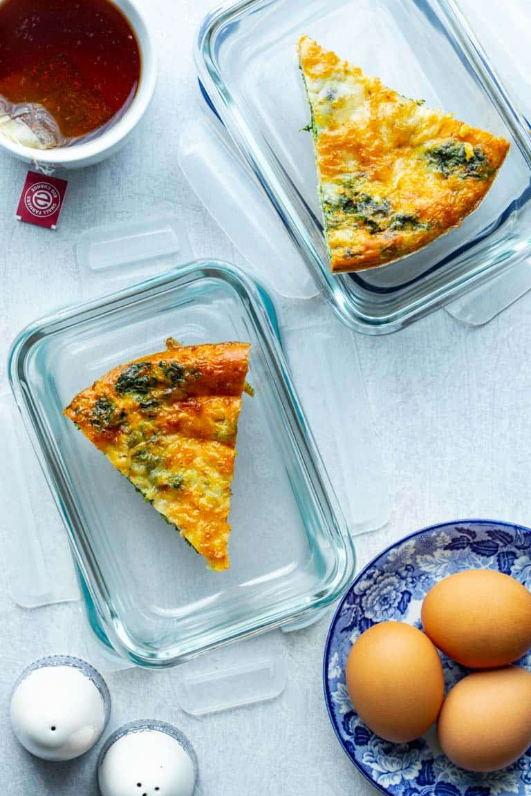 Spinach Egg Bake in two glass resealable containers and a blue and white plate with three eggs on it.