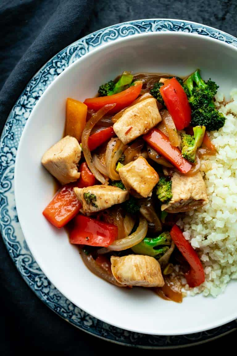 a white bowl with chicken and veggie stir-fry in it