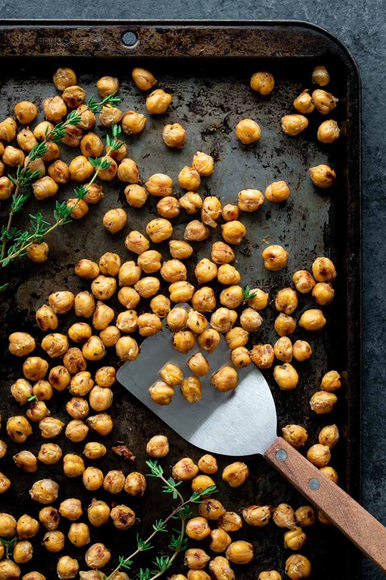 crispy roasted chickpeas and fresh thyme on a baking sheet with a spatula