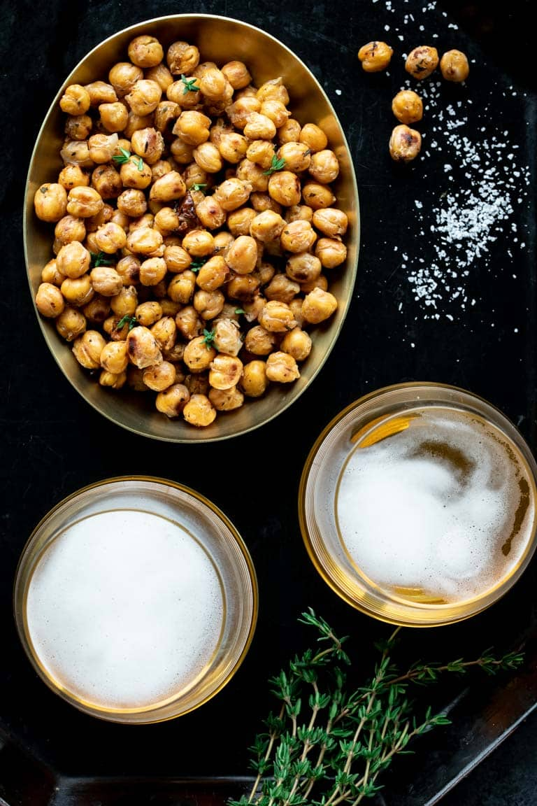 bowl of crispy roasted chickpeas with 2 glasses of beer and salt
