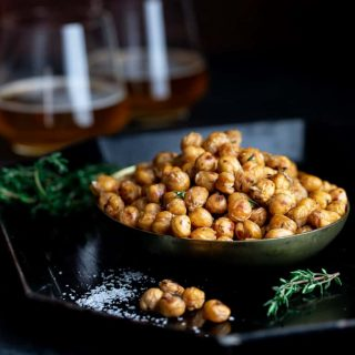 bowl of crispy roasted chickpeas with 2 glasses of beer and fresh thyme