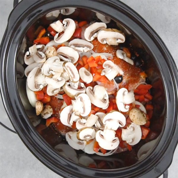 the mushrooms on top of the food in the slow cooker