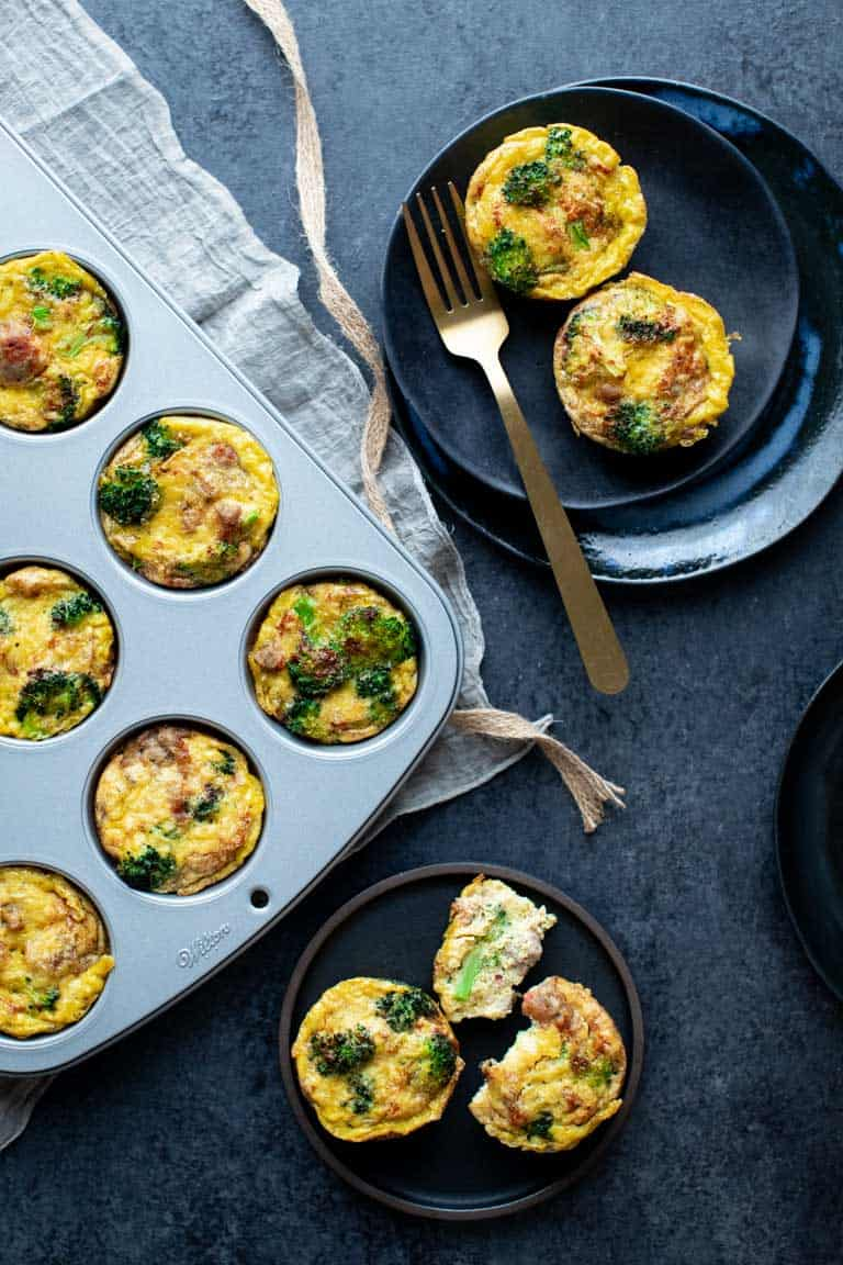 Overhead view of a charcoal gray table with a muffin tin, and two plates of paleo egg muffins