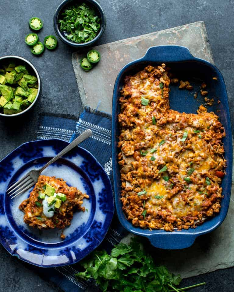 Layered Chicken Enchilada Casserole in a baking dish and plated with cilantro and avocado