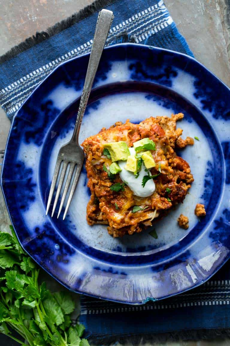 Layered Chicken Enchilada Casserole on a plate with cilantro and avocado