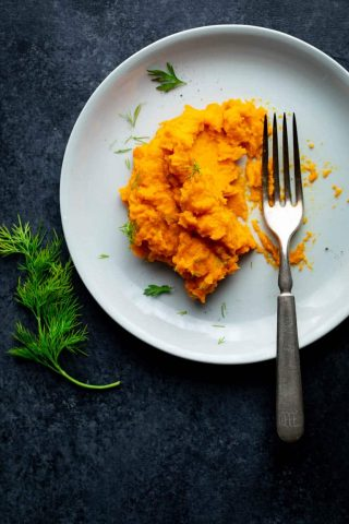 A white plate with mashed parsnips and carrots on it.
