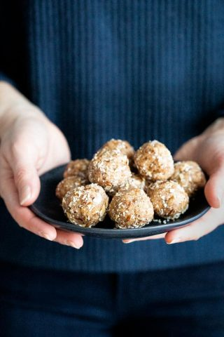 hands holding a plate of paleo energy balls