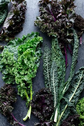 several types of kale on black surface