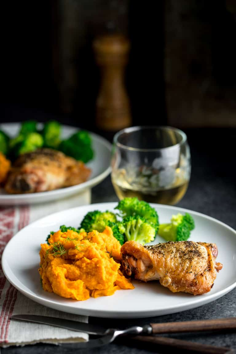 A dinner plate with crispy skin chicken, broccoli and mashed carrots and parsnips