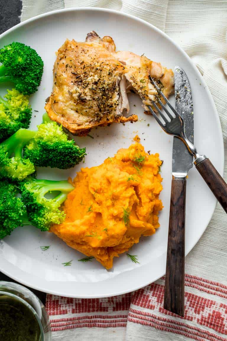 A plate with crispy skin chicken, broccoli and mashed carrots and parsnips