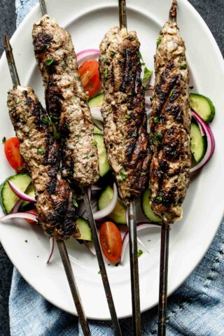 four kofta kebabs on a platter with cucumbers and tomatoes
