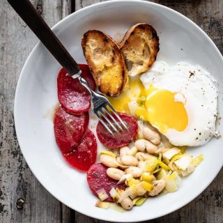 a white bowl with grilled baguette, poached eggs, white beans and sliced beets