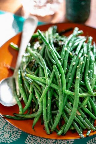 simple skillet green beans on an orange plate