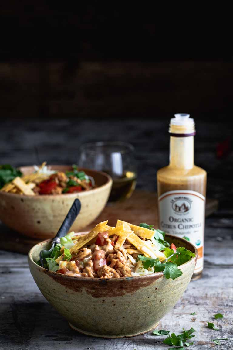 A side view of two bowls of taco salad with a bottle of dressing