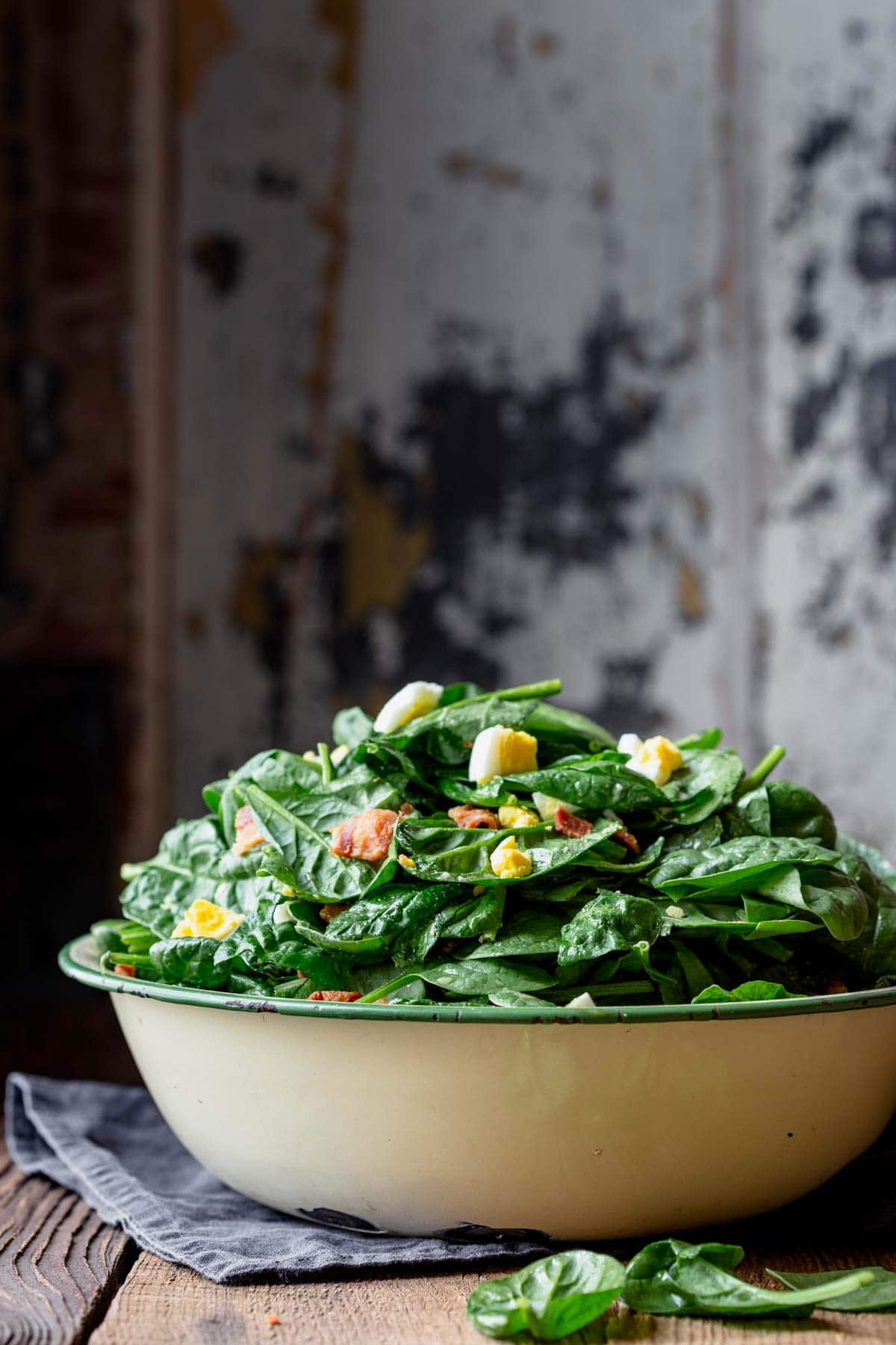 a side view of a bowl of salad piled high with a painterly background