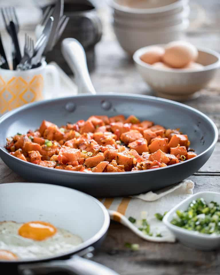 a skillet of sweet potato hash and other breakfast items