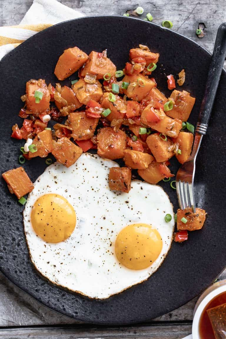 a black plate with breakfast sweet potato hash