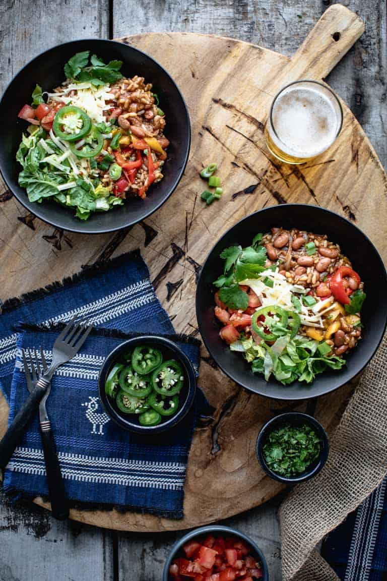 2 vegetarian burrito bowls on a wooden board surrounded by topping ingredients