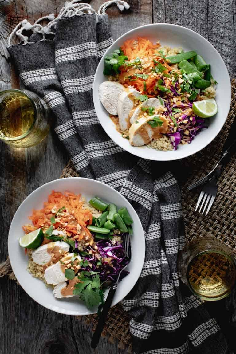 An overhead view of a farm table with two buddha bowls with quinoa and chicken