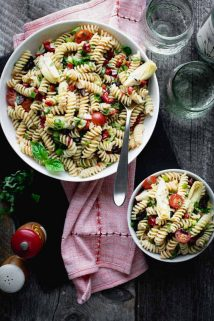 an overhead look at a serving bowl of Italian pasta salad and an individual serving plus a red napkin and two wine glasses