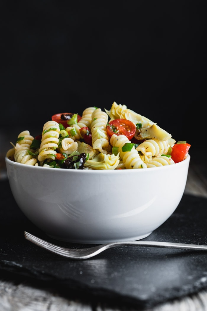 Italian Pasta Salad in a bowl with tomatoes, basil and artichoke Hearts