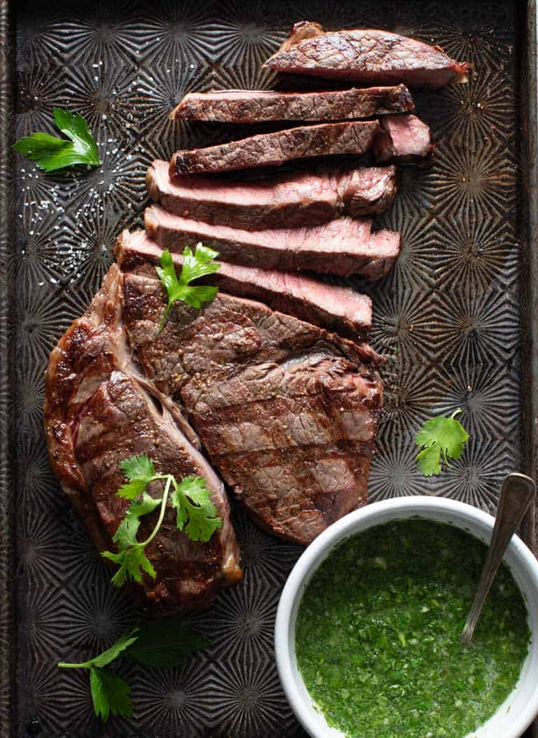 a sliced steak on a black baking sheet with a bowl of chimichurri sauce