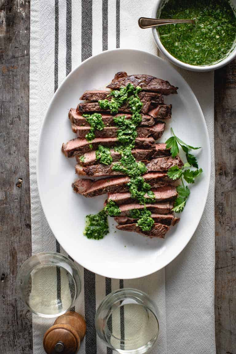 Grilled Sirloin Steak, slices and drizzled with chimichurri sauce on a white dish cloth with black stripes.