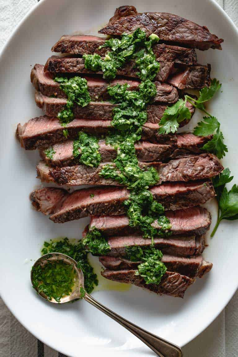 A close up view of sliced grilled sirloin steak with green chimichurri sauce on it