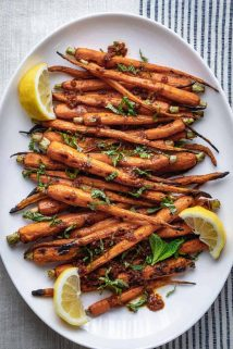 A close-up of a platter of grilled carrots with lemon, harissa and mint.