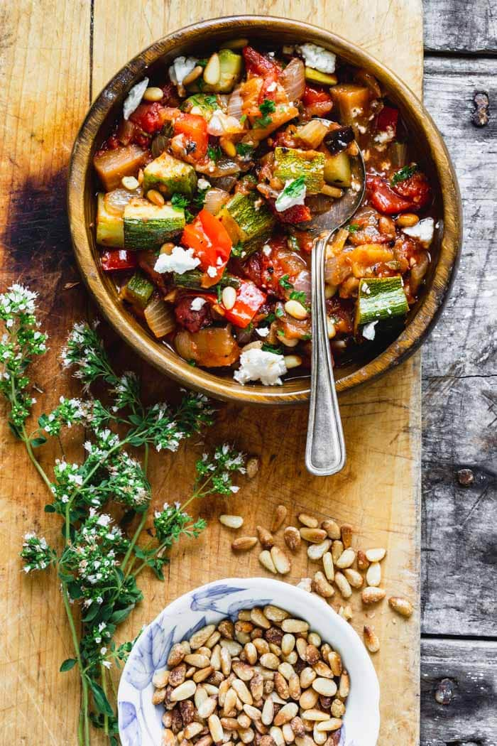 a wooden bowl with a serving of ratatouille. A dish of pinenuts and oregano blossoms.